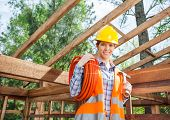image of timber  - Portrait of confident female construction worker holding pipe and hammer in timber cabin at site - JPG