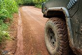 stock photo of dirt road  - The wheels of car go round on dirt road - JPG