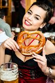 stock photo of pretzels  - Attractive young woman in traditional Dirndl eating Oktoberfest Pretzel and drinking beer - JPG