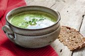 picture of vegetable soup  - green vegetable cream soup with broccoli rucola and spinach in a ceramic bowl red towel on a rustic wooden table - JPG