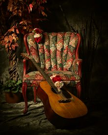 stock photo of edwardian  - A vintage acoustic guitar leans against an empty antique patterned armchair - JPG