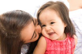 picture of mother child  - photo of a Mother kissing her daughter  - JPG