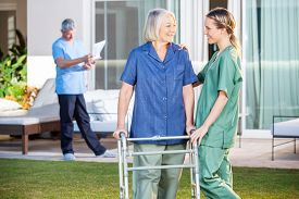 picture of nursing  - Friendly female nurse assisting senior woman to walk with Zimmer frame in lawn at nursing home - JPG