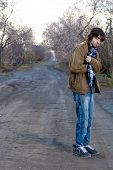 picture of young men  - the standing young man on dirty road