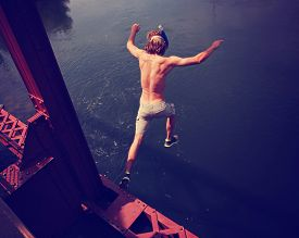 pic of trestle bridge  - a boy jumping of an old train trestle bridge into a river toned with a retro vintage instagram filter effect app or action on a hot summer day - JPG