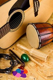 image of bongo  - Vertical photo with set of musical instruments on wooden OSB board as green egg shaker guiro bongo drum few guitar picks harmonica and acoustic guitar - JPG