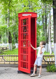 image of phone-booth  - the boy speaks on his mobile phone at a phone booth in the British style - JPG