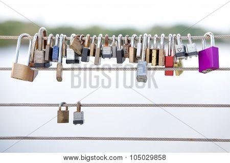 Постер, плакат: Love Locks Hanging From A Cable Railing, холст на подрамнике