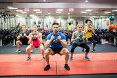 Fit people working out in fitness class at the gym poster