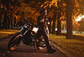 Постер, плакат: Motorcyclist With A Cafe racer Motorcycle Outdoors