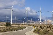 stock photo of wind-power  - wind turbines on a hillside producing clean energy - JPG