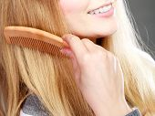 Постер, плакат: Closeup Woman Combing Her Hair With Comb