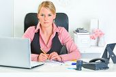 Authoritative modern business woman sitting at office desk