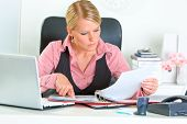 Concentrated modern business woman sitting at office desk and working with financial documents