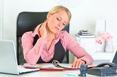 Tired modern business woman sitting at office desk and working with financial documents