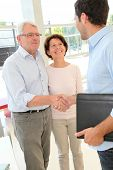 stock photo of 55-60 years old  - Senior couple signing contract - JPG