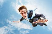 stock photo of parachute  - Conceptual image of young businessman flying with parachute on back - JPG