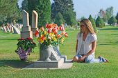 stock photo of headstones  - Young woman sitting near headstone in cemetery - JPG