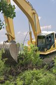picture of bulldozer  - Heavy equipment strips all the vegetation off the side of a hill - JPG
