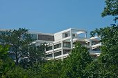 White Terraced Office Building Rising Out Of Trees Into Blue Sky