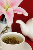 pic of stargazer-lilies  - A cup of Chinese green tea with a teapot and stargazer lily in the background - JPG
