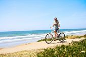 Woman on a Bicycle Ride along the beach