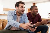 Two Male Friends Sitting On Sofa In Lounge Playing Video Game poster