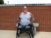 stock photo of amputee  - A disabled Vet in front of a sign that says it all - JPG
