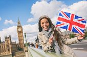 London travel tourist woman showing Union flag Great Britain british UK flag. Asian girl at Big Ben  poster