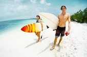 Two happy surfers, caucasian man and woman smile and walk with their surf boards along the sandy bea poster
