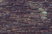 Old Brick Wall Background. Dark Brown Rough Stone Wall. Rock Wall Surface. Stony Texture. Grunge Mat poster