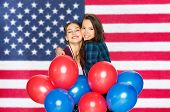 independence day, national holiday and 4th july party concept - happy smiling pretty teenage girls w poster