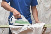 Man Ironing Shirt On Ironing Board. Handsome Man Ironing White Shirt poster