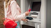 Woman Traveler Takes Out Money At An Atm In Europe poster