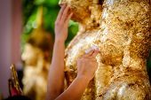 Thai People Make Merit, Buddhists Gilding Gold Leaf On The Face Of Buddha Statue To Worship Buddha I poster