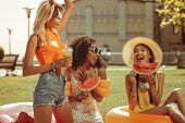Energetic Three Girls Having Fun During A Picnic Outdoors poster