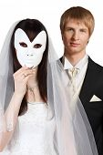 Beautiful bride hid her face behind white mask; groom stands behind her isolated on white background