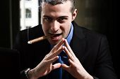 stock photo of delinquency  - Shady man smoking a cigar in his office - JPG