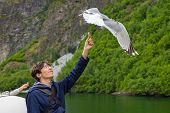 Young Man Feeding Seagulls Flying Over The Ferry Boat. Young Male Tourist On The Deck Of A Ferry In  poster