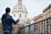 Portrait of a handsome, young, male tourist in Rome, Italy (dome of the Santissimo Nome di Maria chu
