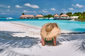 Woman sitting on beach under palm tree. Summer vacation at Maldives. poster