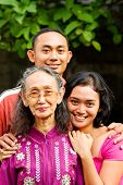Happy Asian Young Man And Woman Embrace Old Mother