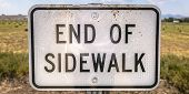 End Of Sidewalk Sign In Front Of A Grassy Terrain poster