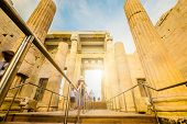 Tourists pass through the Propylaea monumental entrance to the Parthenon temple in Athens, Greece poster