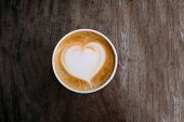 Paper Cup Of Fresh Delicious Cappuccino Coffee With Beautiful Latte Art In The Shape Of Heart On Dar poster