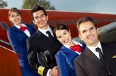 image of cabin crew  - Friendly cabin crew smiling with an airplane at the background - JPG