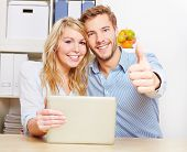 Happy couple holding thumbs up with smartphone and tablet PC in the living room