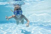 young child diving underwater in mask in pool