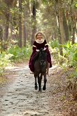 woman in medieval dress riding galloping horse through forest