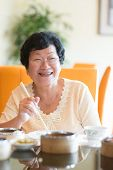 Happy 60s Senior Asian Woman dining indoors